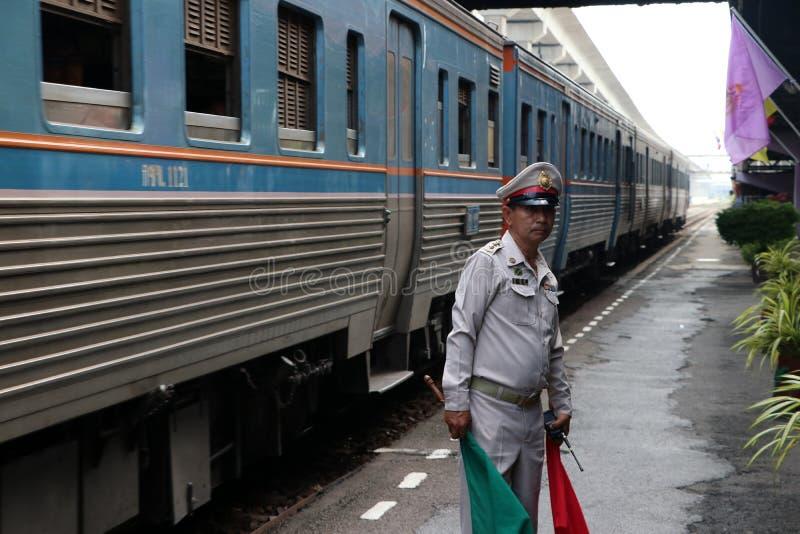 有红色和绿色旗子的在手上,发信号乘客和人的安全预防措施的代理人火车官员,当时 免版税图库摄影