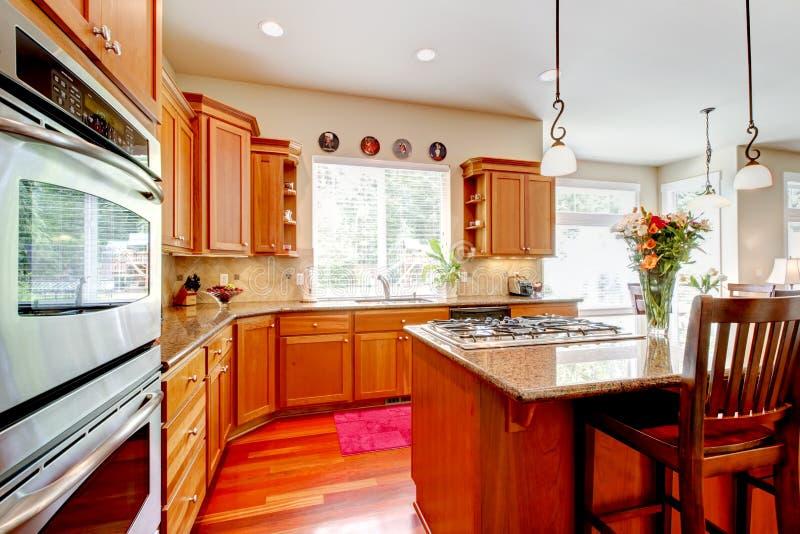 有红色和花岗岩的木豪华大厨房。 免版税库存照片