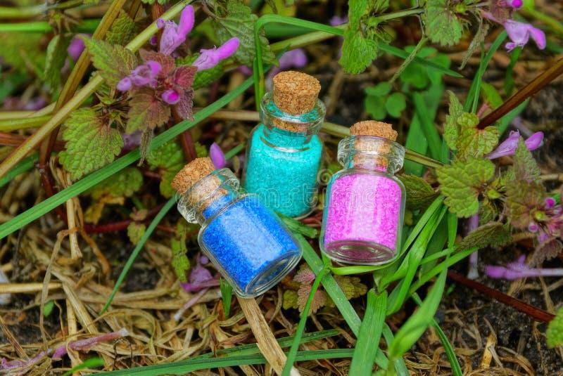 有红色和蓝色沙子的三个小玻璃瓶在草植物和淡紫色花中 库存图片