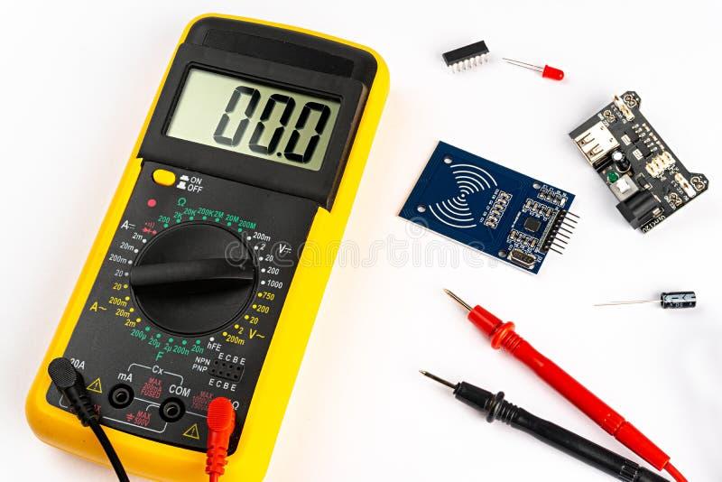 有红色和黑缆绳microc基片电路板的黄色数字式多用电表电子测量设备工具带领了和微小 免版税库存照片