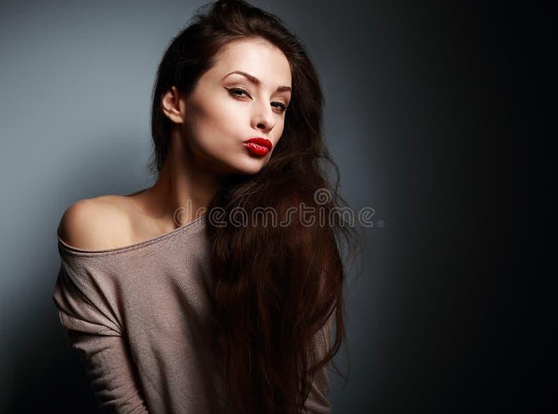 有红色唇膏的性感的做鬼脸的少妇在黑暗 库存照片