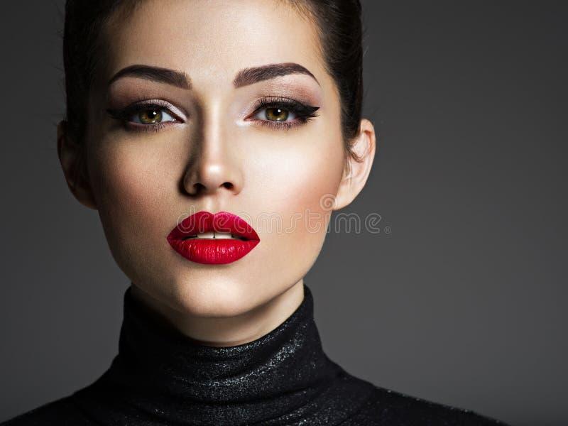 有红色唇膏的美丽的年轻时尚妇女 免版税库存照片