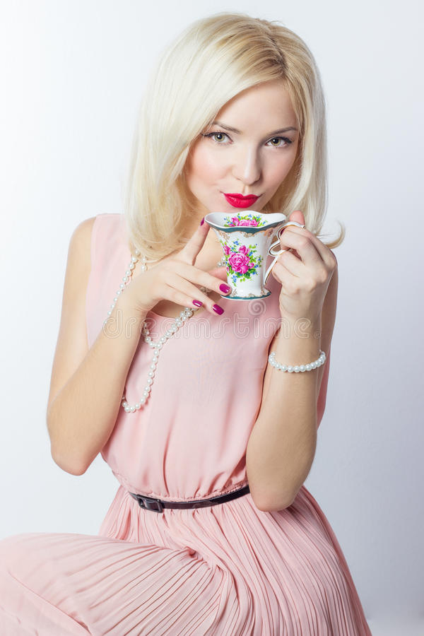 有红色唇膏的美丽的微笑的愉快的性感的典雅的女孩在减速火箭的样式的一件桃红色礼服喝从的茶咖啡小杯子 库存照片