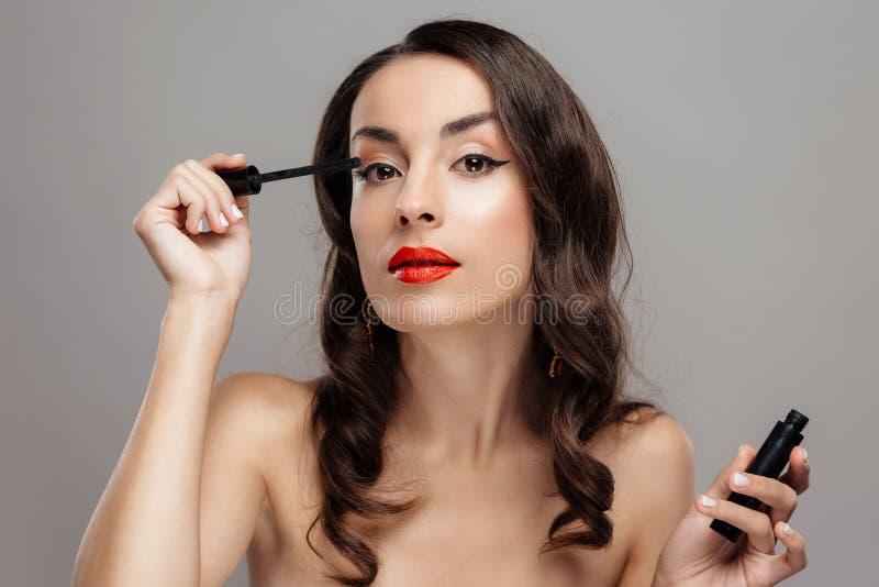 有红色唇膏的美丽的深色的妇女在嘴唇 有美好的构成的特写镜头女孩 库存图片