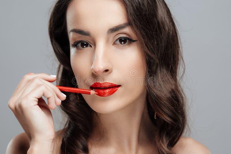 有红色唇膏的美丽的深色的妇女在嘴唇 有美好的构成的特写镜头女孩 免版税库存照片