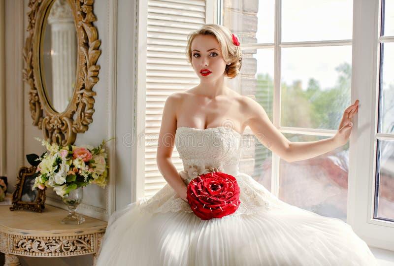 有红色唇膏的迷人的美丽的年轻白肤金发的女孩在我的嘴唇 库存照片