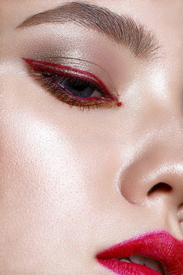 有红色嘴唇和红色箭头的女孩在眼睛前面 与构成裸体和光亮的皮肤的美好的模型 在st拍的照片 免版税库存照片
