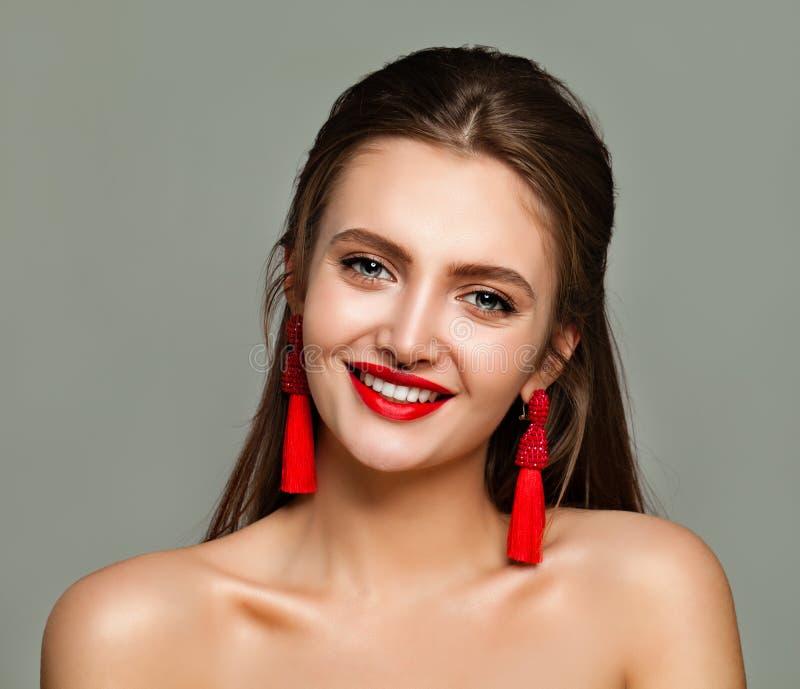有红色嘴唇构成和首饰耳环的年轻快乐的妇女 免版税库存照片