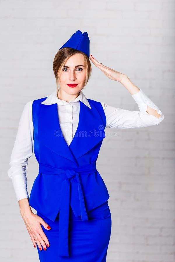 有红色嘴唇的一位可爱的空中小姐在一件蓝色制服和盖帽握她的手到她的寺庙 免版税图库摄影