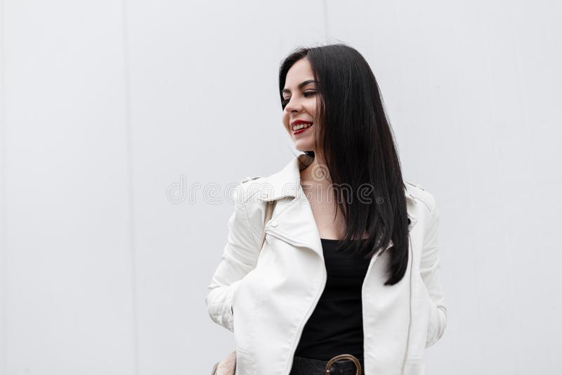 有红色嘴唇的俏丽的年轻快乐的妇女有在一件时兴的夹克的有吸引力的微笑的在摆在白色墙壁附近的T恤杉 库存图片