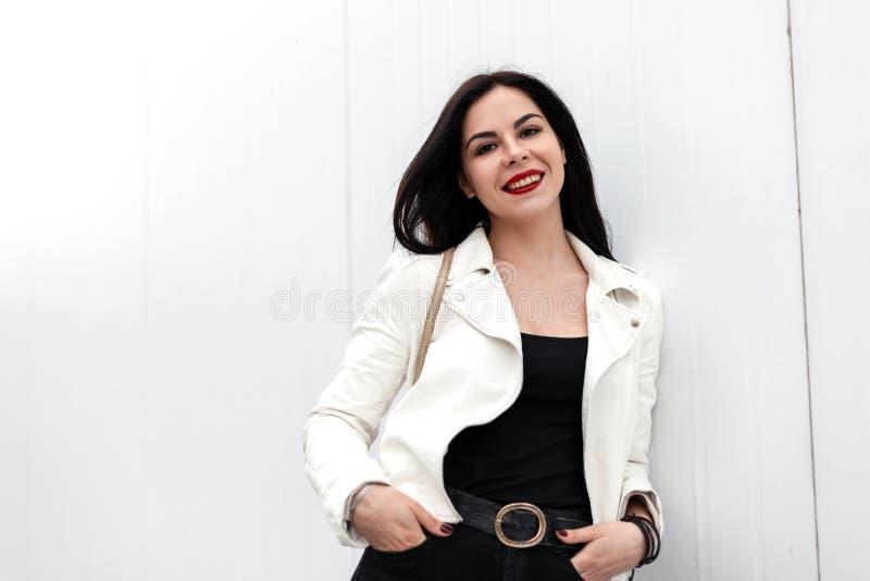 有红色嘴唇的俏丽的年轻快乐的妇女有在一件时兴的夹克的美好的微笑的在牛仔裤的葡萄酒T恤杉 免版税库存照片