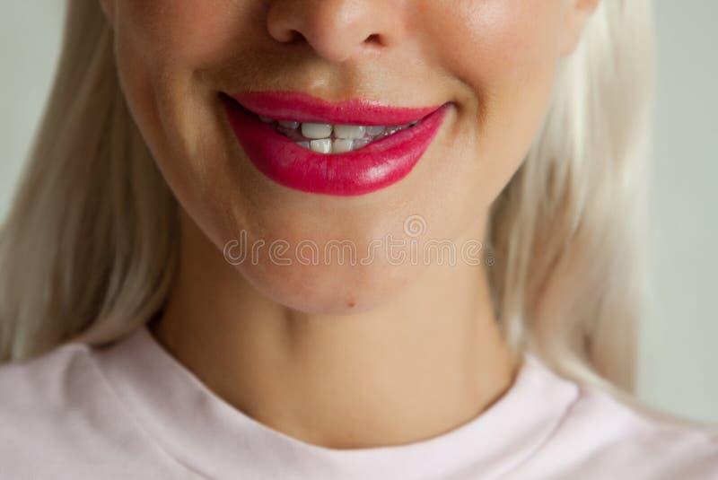 有红色嘴唇的微笑白肤金发的妇女,自然牙 免版税库存图片