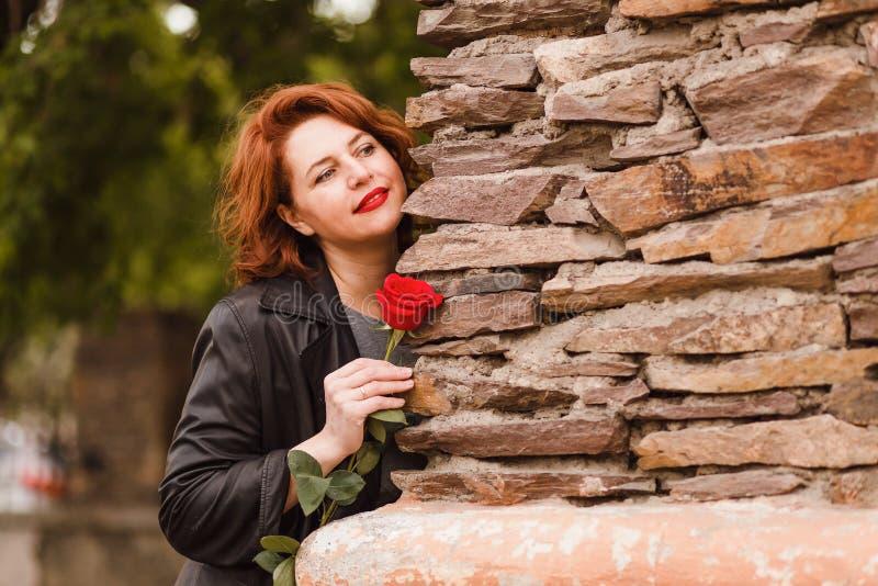 有红色嘴唇的微笑的中年妇女在拿着一朵红色玫瑰的一个皮革黑斗篷 库存图片