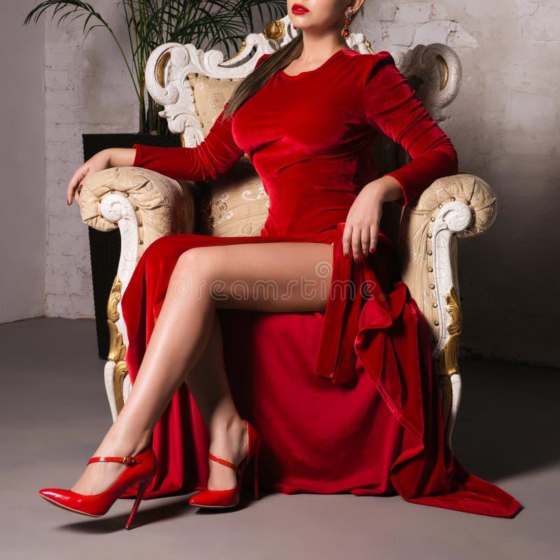有红色嘴唇的性感的魅力妇女在典雅的红色礼服坐扶手椅子在顶楼演播室 库存图片