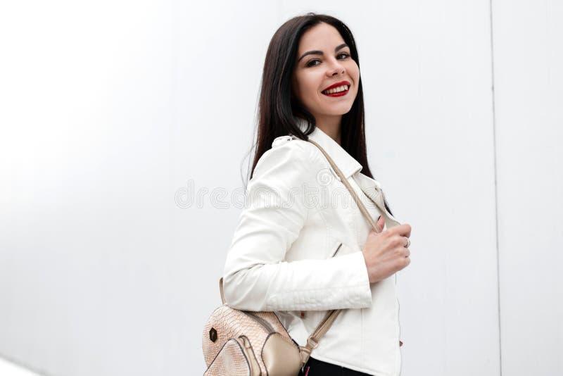 有红色嘴唇的逗人喜爱的快乐的年轻女人有在一件时髦的夹克的正面微笑的有在一个白色大厦附近的一个时髦背包的 免版税库存照片