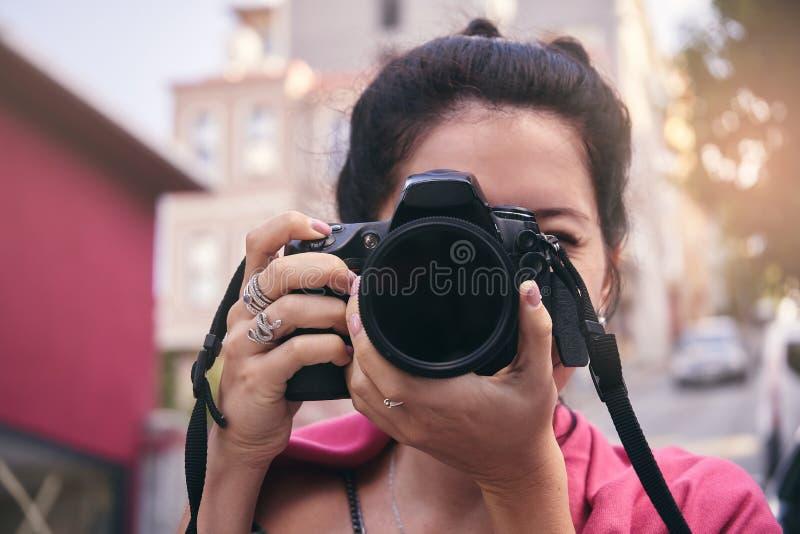 有红色围巾的妇女摄影师,为老镇照相 免版税库存图片