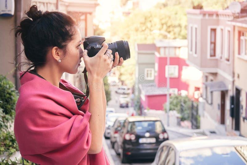 有红色围巾的妇女摄影师,为老镇照相 免版税库存照片