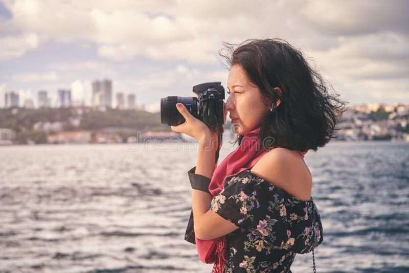 有红色围巾的妇女摄影师,为风景照相在海附近在日落 免版税库存图片