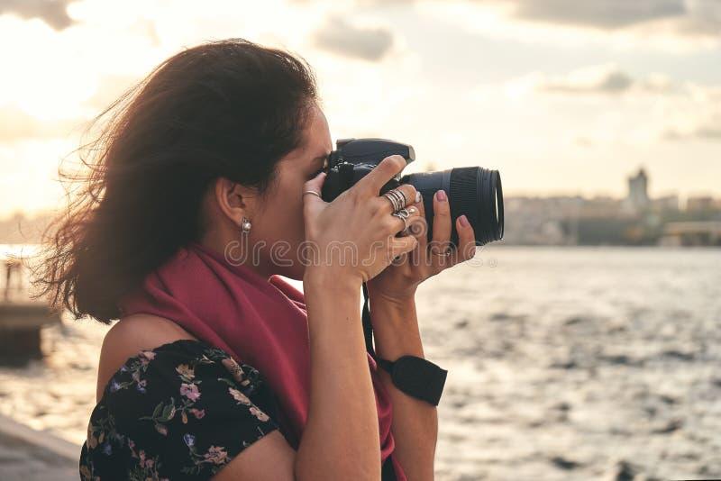有红色围巾的妇女摄影师,为风景照相在海附近在日落 免版税图库摄影