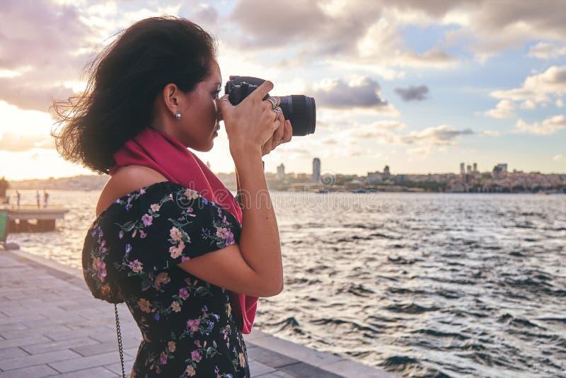 有红色围巾的妇女摄影师,为风景照相在海附近在日落 库存图片