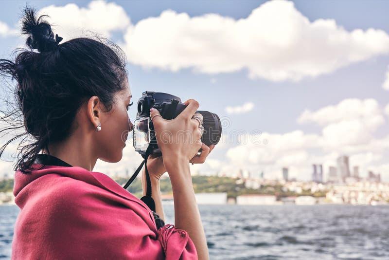 有红色围巾的妇女摄影师,为风景照相海上 库存图片