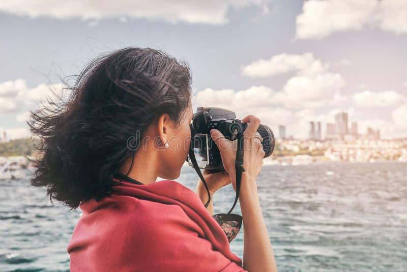 有红色围巾的妇女摄影师,为风景照相海上 免版税库存图片