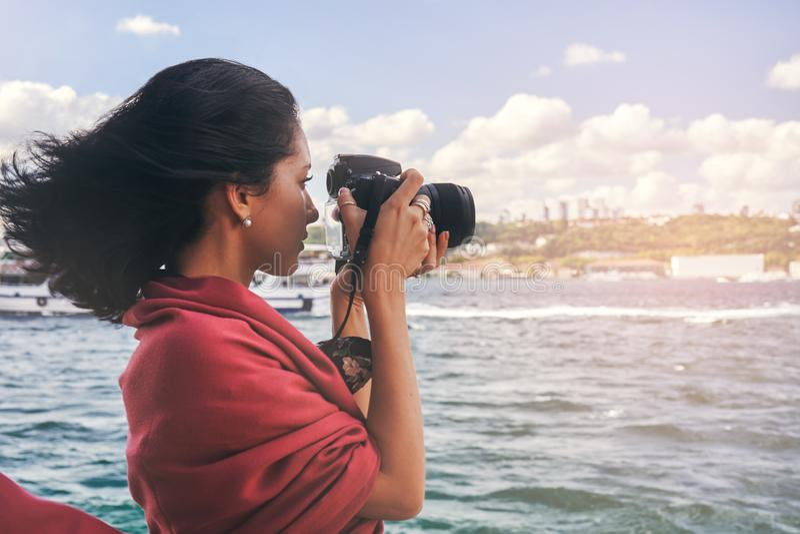 有红色围巾的妇女摄影师,为风景照相海上 免版税图库摄影
