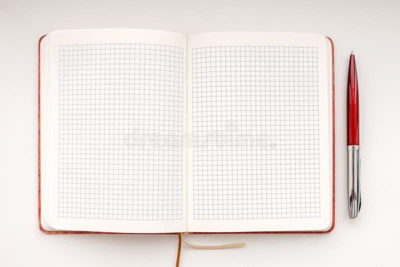 有红色圆珠笔的开放笔记本在白色背景,顶视图 免版税库存图片