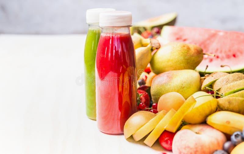 有红色圆滑的人和汁液饮料的瓶在白色桌背景用夏天果子和莓果,正面图 健康的食物 免版税库存照片