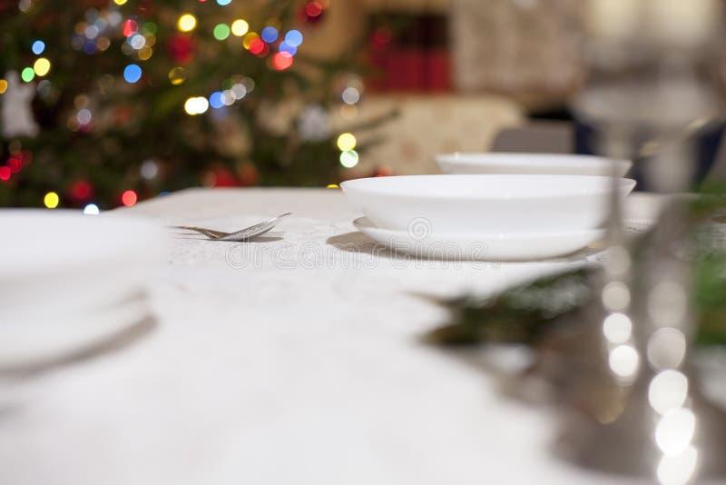有红色圣诞树的在背景中,在白色桌设置的圣诞节锥体匙子 安置文本 在视图之上 免版税库存照片