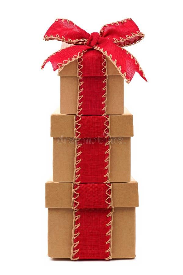 有红色在白色隔绝的弓和丝带的被堆积的棕色礼物盒 图库摄影