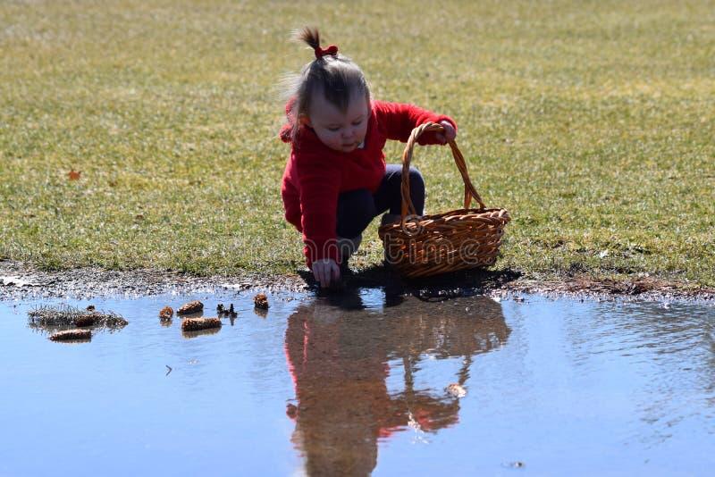 有红色外套的小孩下跪在水反射的 免版税库存图片