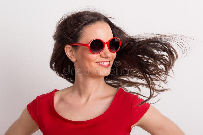 有红色太阳镜和T恤杉的一名年轻美丽的高兴妇女在演播室 免版税库存图片