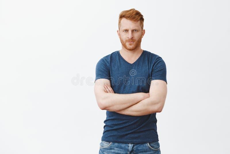 有红色头发和刺毛的,皱眉悦目严肃的男性保镖,看从严密的前额下面照相机 库存图片