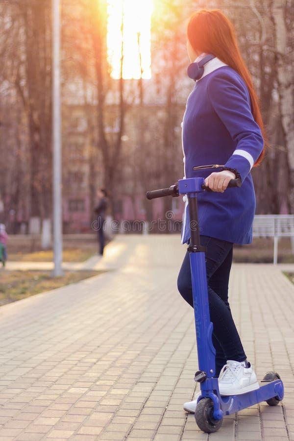 有红色头发的一名年轻白种人妇女在一辆蓝色电滑行车的一件蓝色外套在公园 环境友好的运输 免版税库存照片