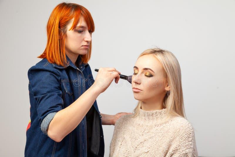 有红色头发的化妆师女孩在与闭上的眼睛的一个白肤金发的模型在她的手上投入构成,拿着一把刷子并且申请脸红 图库摄影