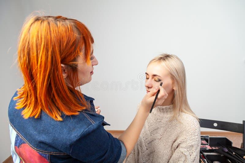 有红色头发的化妆师强加构成给与刷子的闭合的眼睛应用在眼皮的阴影在东方样式: 免版税库存照片
