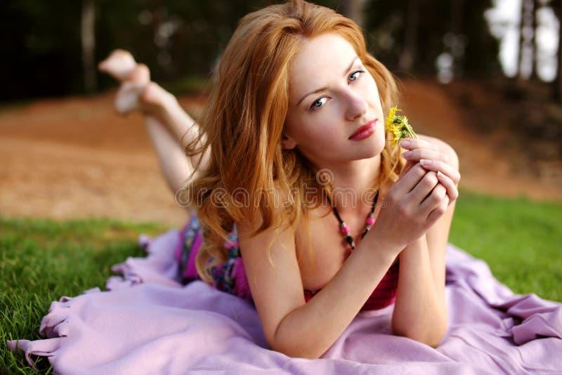 有红色头发的女孩在绿草 库存照片