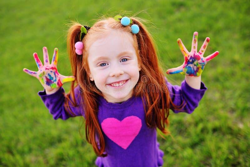 有红色头发的小女孩显示她手肮脏与多彩多姿的油漆和微笑 免版税库存图片