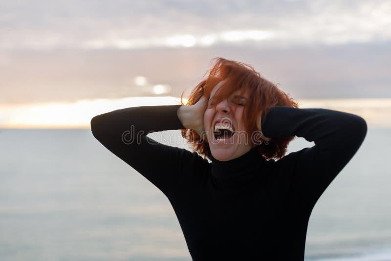 有红色头发的年轻女人抓住她的头和响亮地尖叫从在海和日落背景的心伤  免版税库存照片