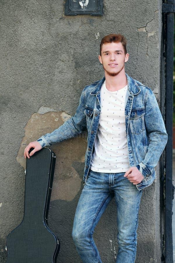 有红色头发的年轻快乐的人在有一把吉他的门在案件 库存照片