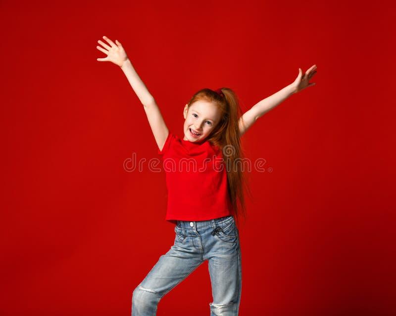 有红色头发的微笑对照相机的一少女的画象用手在天空中 库存照片