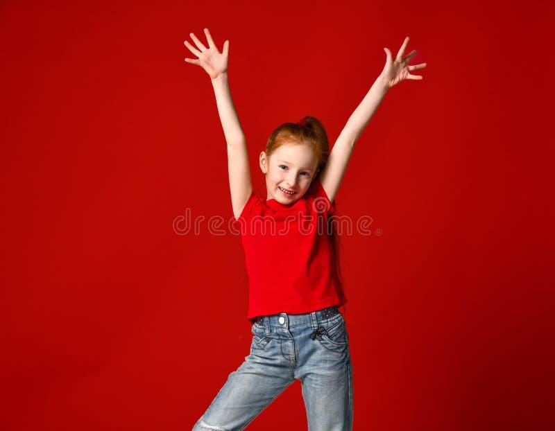 有红色头发的微笑对照相机的一少女的画象用手在天空中 免版税库存照片