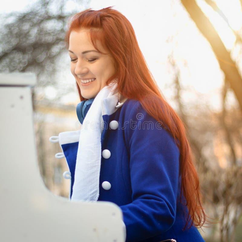 有红色头发的欧洲白种人女孩妇女微笑并且弹钢琴在公园在日落 现代和古典音乐 免版税图库摄影