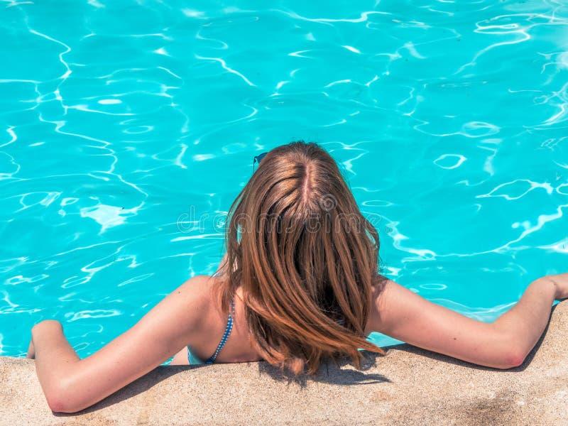 有红色头发的白种人女孩,摆在与她的移动她的头发的后面和与蓝色游泳衣 图库摄影