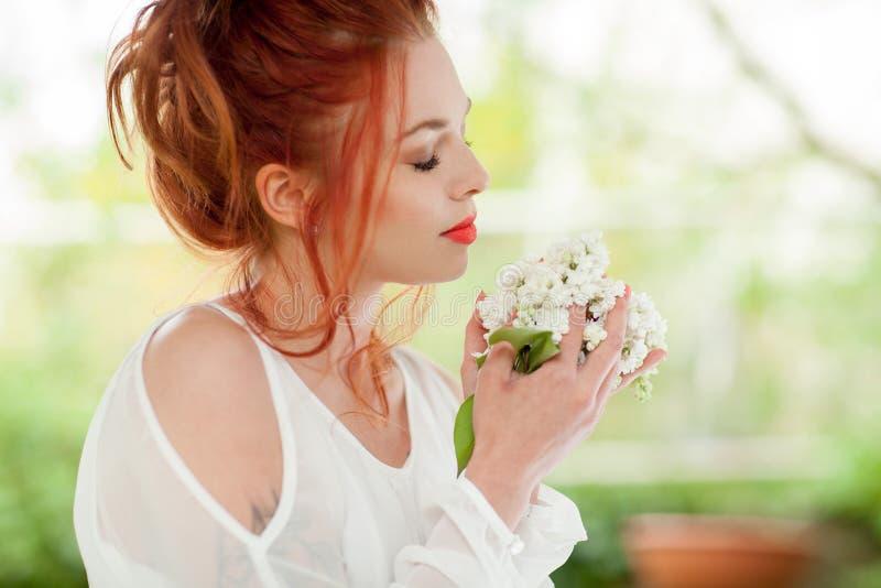 有红色头发的美丽的妇女在她的手上的拿着白色淡紫色绽放 免版税库存照片