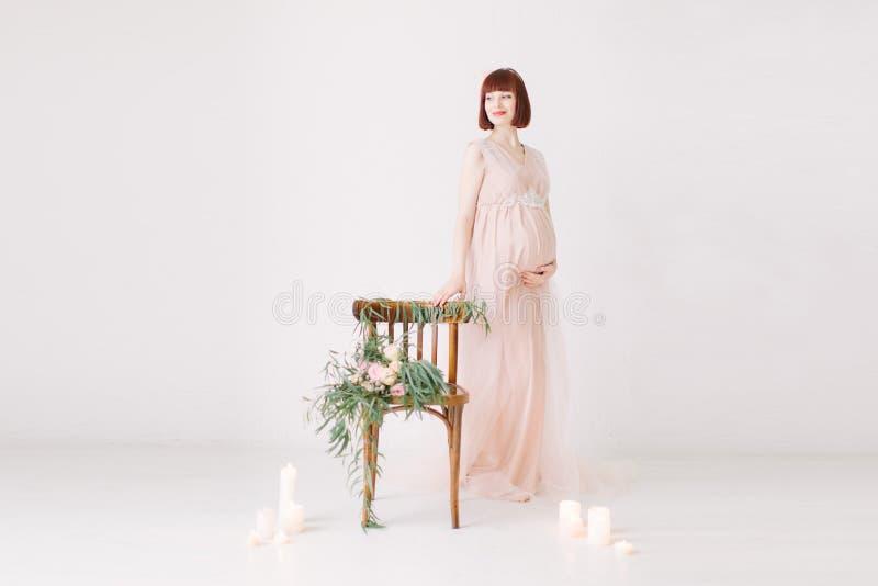 有红色头发的美丽的孕妇支持有装饰的椅子的白色墙壁 库存图片