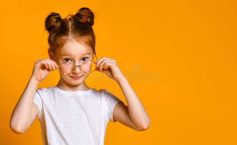 有红色头发的美丽的少女用在她时髦的玻璃的一个百吉卷看您框架的 免版税库存图片