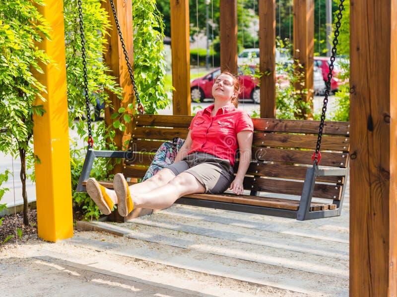 有红色头发的美丽的年轻女人坐一条长凳在城市公园,女孩放松 库存图片