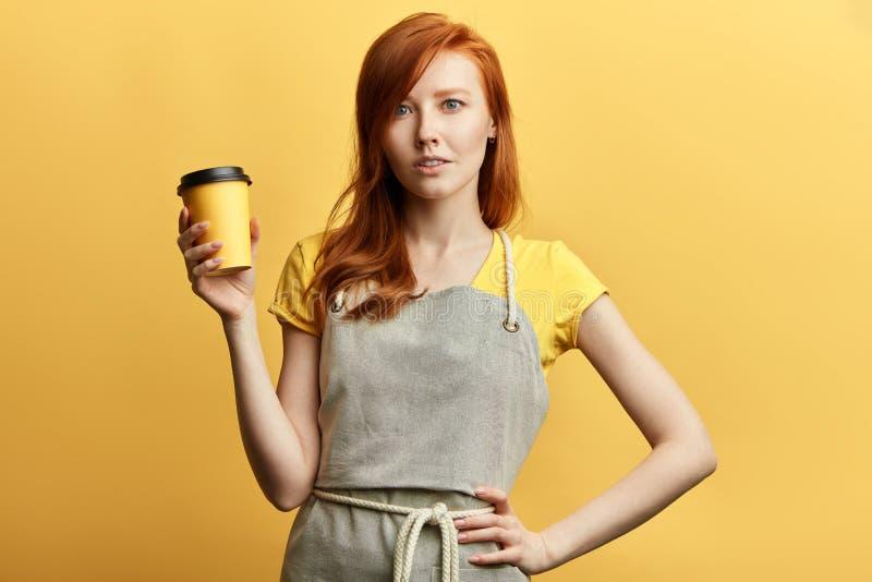 有红色头发的美丽的年轻女人微笑和调查照相机的 免版税图库摄影